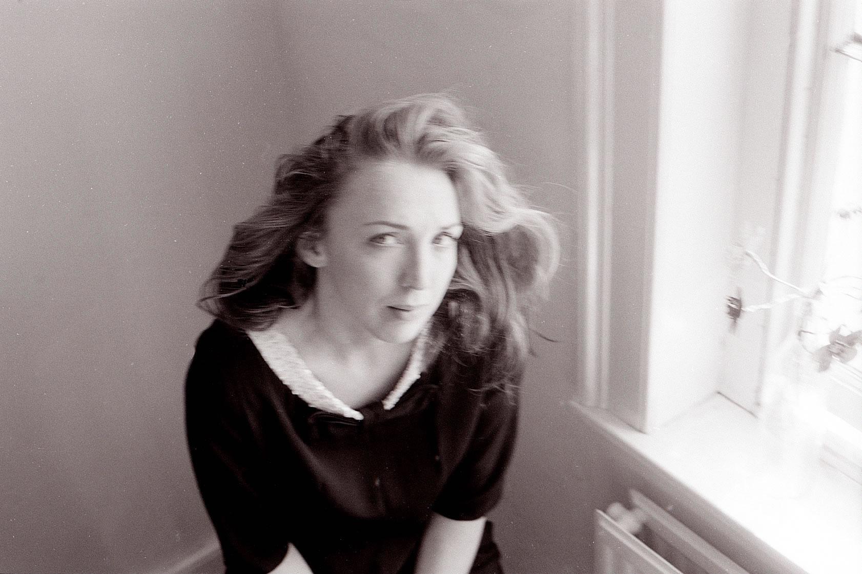 GIRL AT WINDOW IN BLACK DRESS