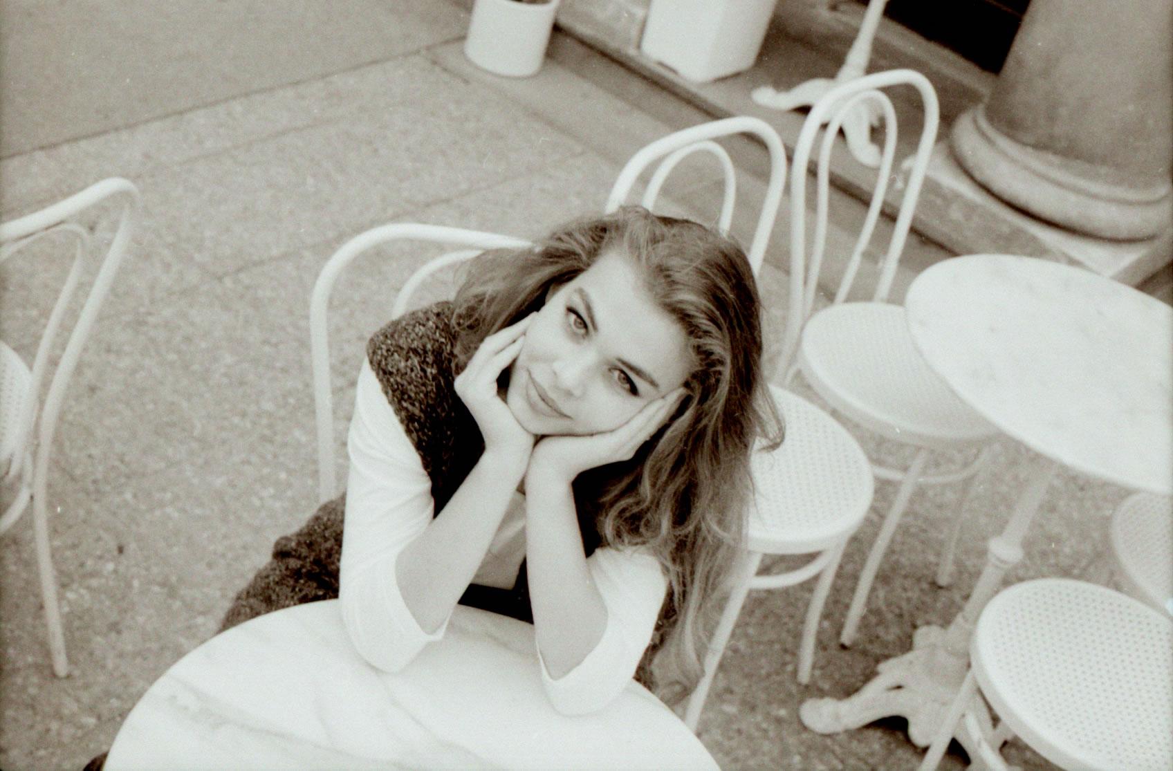 GIRL AT CAFE TABLE PRAGUE SMILES AT CAMERA